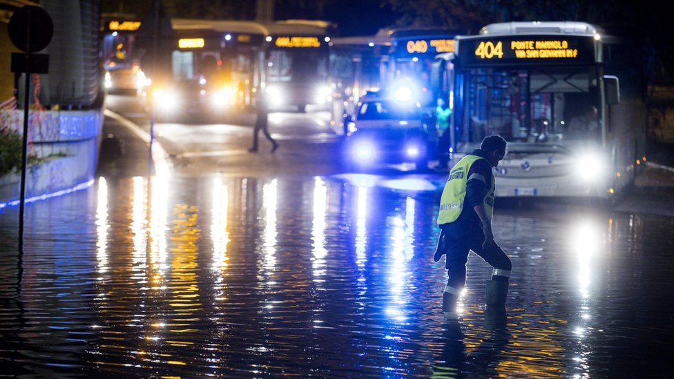 An Italian policeman works in a flooding street in Rome
