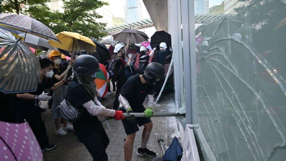 Manifestantes rompiendo cristales para entrar al edificio