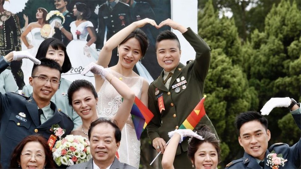 同婚新人少校政戰官王翊和伴侶孟酉玫拿著彩虹旗參加婚禮(Credit: EPA)