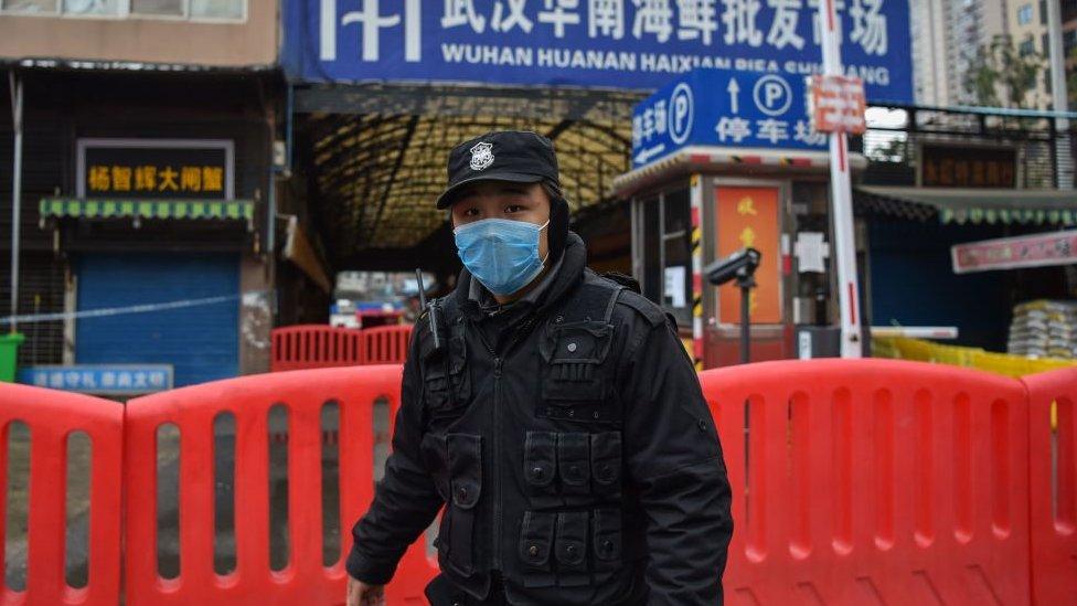 Policía usando máscara en frente de la entrada al mercado de Wuhan.