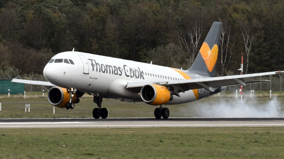 A Thomas Cook plane touches down on a runway.