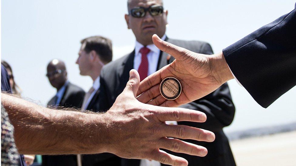 Mano presidencial con una moneda.
