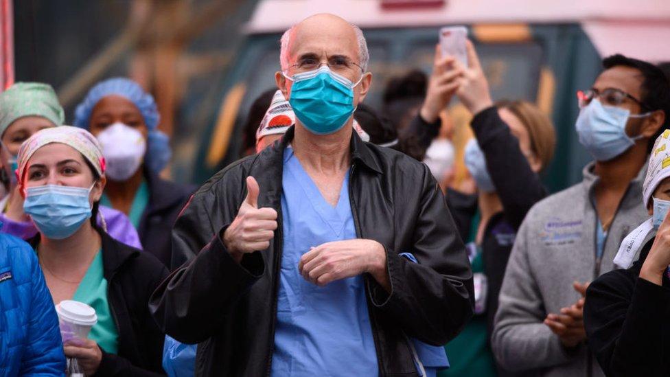 Trabajadores médicos frente al hospital Langone Health de Nueva York mientras la gente aplaude para mostrar su gratitud al personal médico y a los trabajadores esenciales en la primera línea de la pandemia de coronavirus el 19 de abril de 2020 en la ciudad de Nueva York.