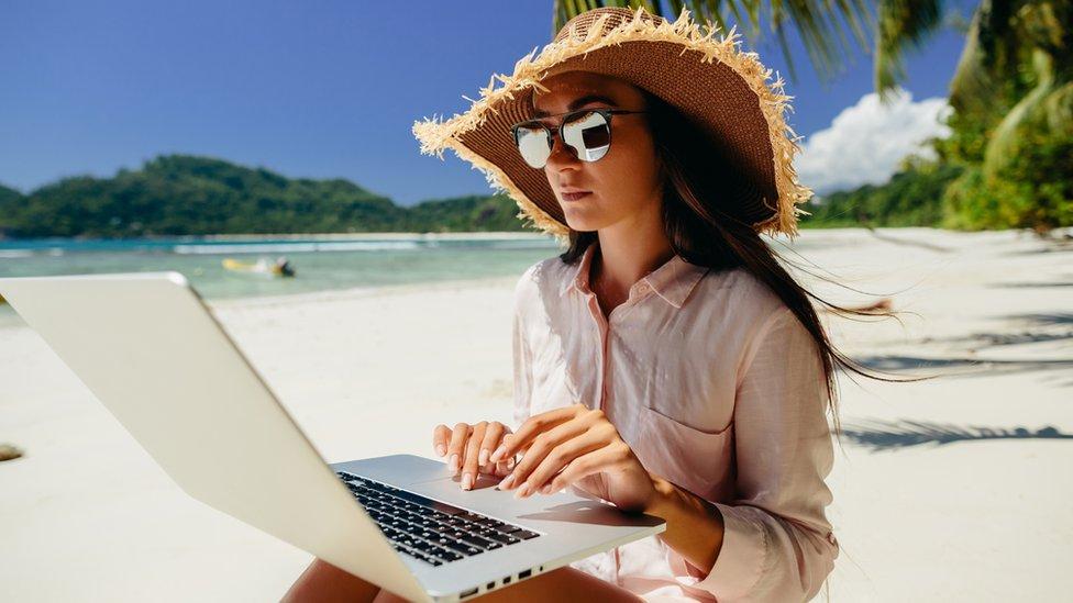Una mujer con lentes de sol y sombrero trabaja con una computadora en una playa.