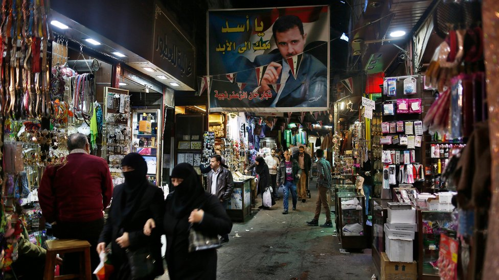 """A poster of the Syrian President Bashar Assad that reads """"Assad we are with you for ever"""" in Arabic hangs at the popular Hamidiyeh old market in Damascus"""