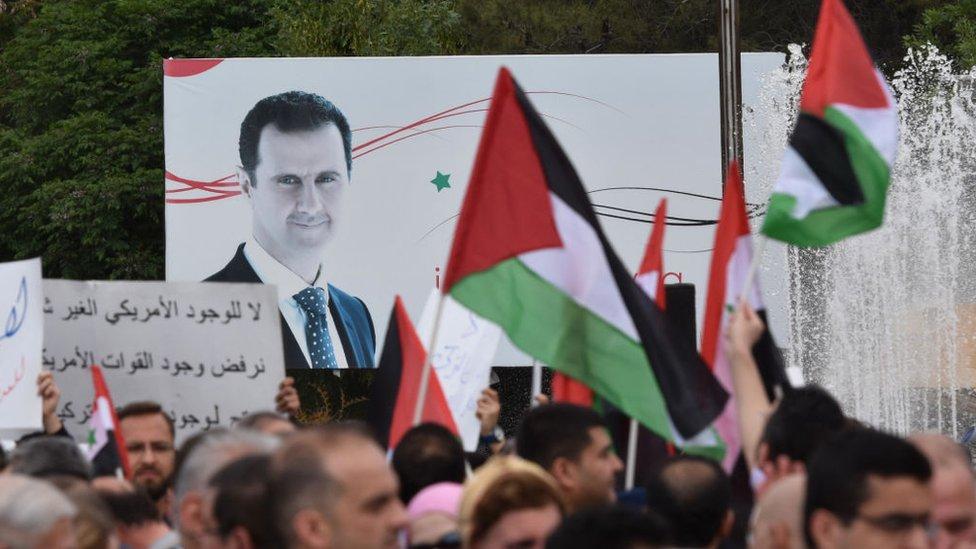 Letrero con la imagen de Bashar al Asad, rodeado de sus seguidores.