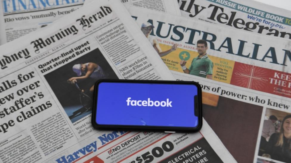 Logo de Facebook en un celular sobre periódicos.