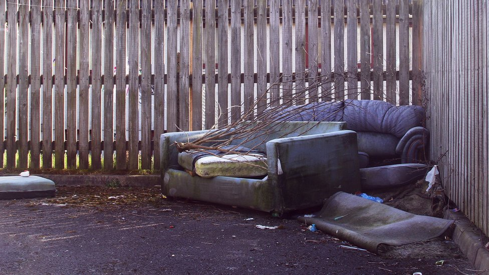 Sofas abandoned against a fence