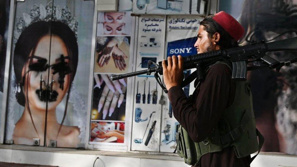Un talibán pasa frente a un salón de belleza vandalizado