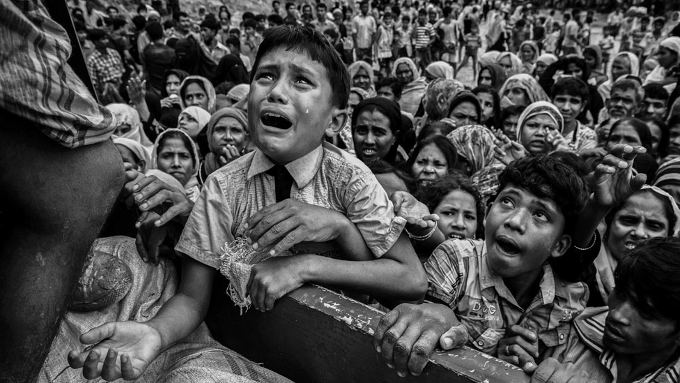 A Rohingya refugee cries as he climbs on a truck distributing aid for a local NGO near the Balukali refugee camp