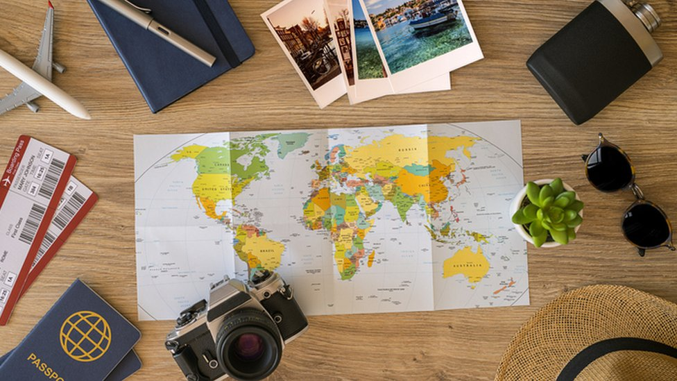 World map surrounded by holiday items like passport, sun glasses, camera and plane tickets