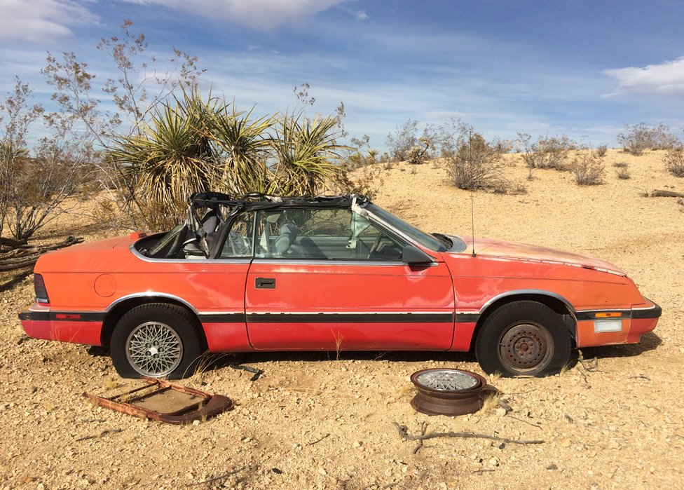 A red car is seen abandoned in the desert