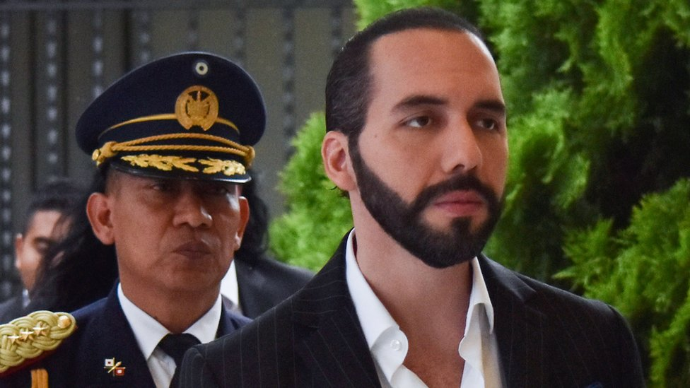 Nayib Bukele y un funcionario de seguridad detrás