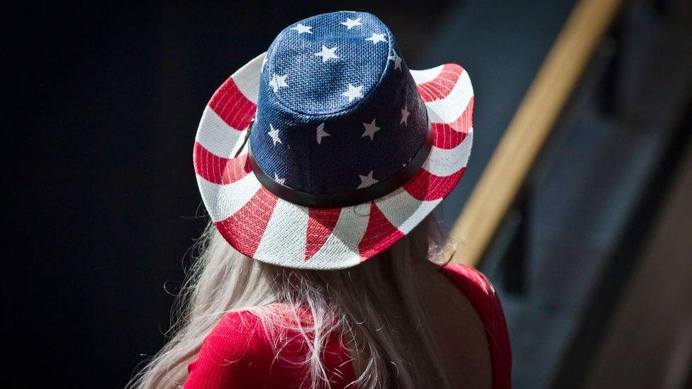 Mujer de espaldas con un sombrero con los colores de la bandera de Estados Unidos.
