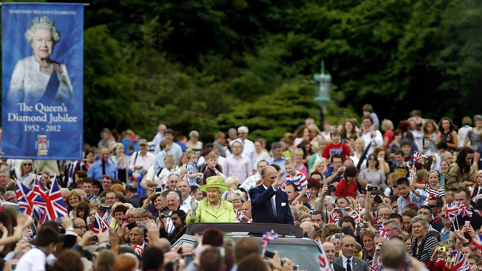 The Queen and Prince Phillip waving from a car amidst crowds
