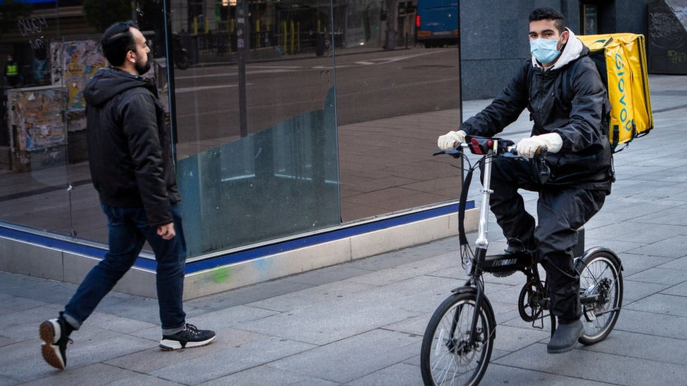 Un repartidor con mascarilla en una calle de Madrid.