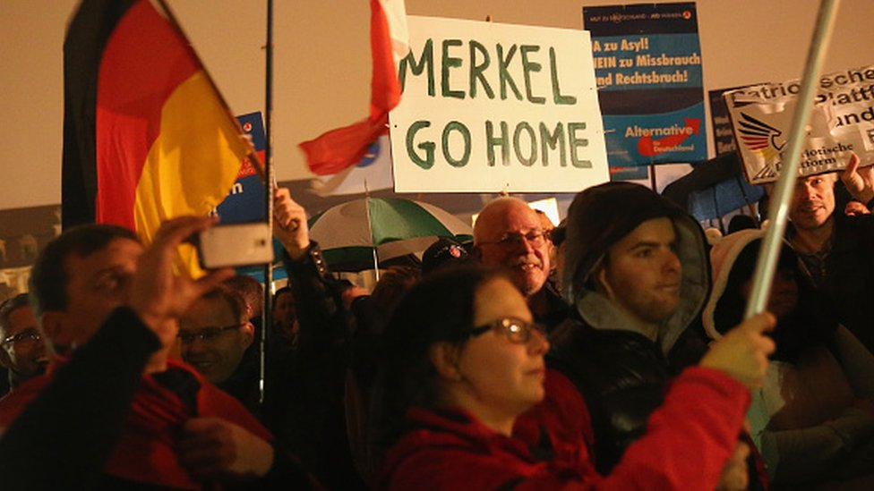Supporters of the AfD political party protest against German Chancellor Angela Merkel's liberal policy towards taking in migrants and refugees