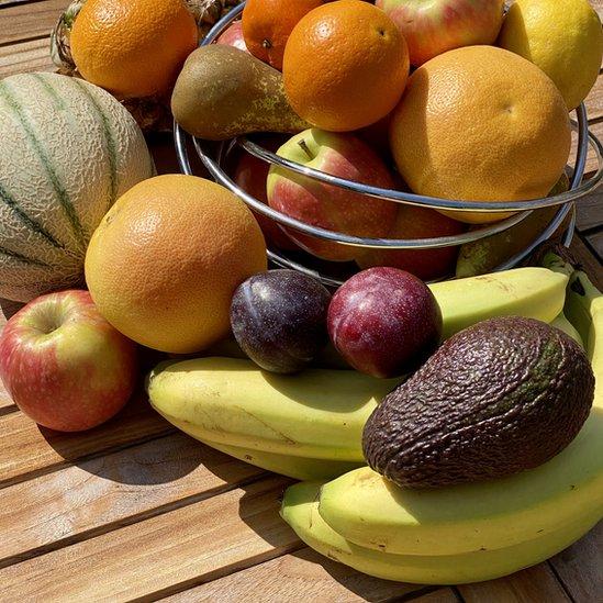 Grupo de frutas, incluyendo aguacate, plátano, ciruela y naranja