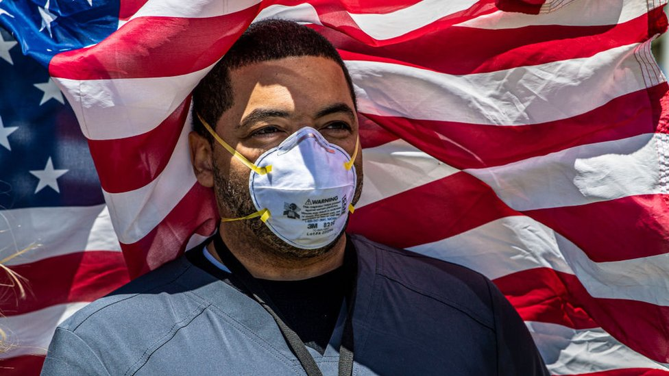 Hombre con mascarilla y bandera de EE.UU. detrás.