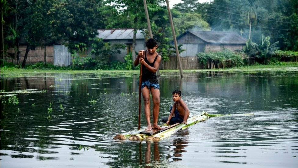 Indian children paddle a raft through floodwaters at Kalgachia in Barpeta district in India's northeastern state of Assam, on July 12, 2019.