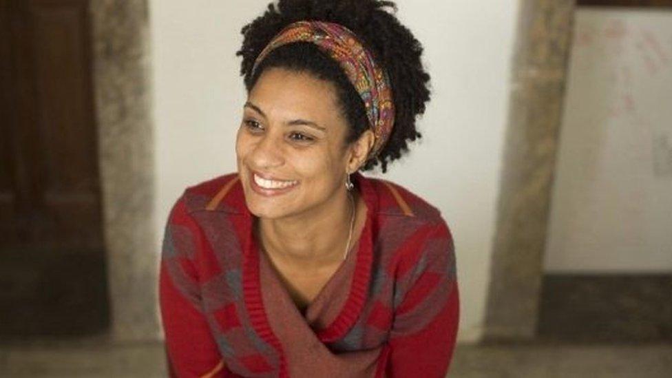 A vereadora Marielle Franco, uma mulher negra jovem e sorridente, com uma faixa nos cabelos crespos