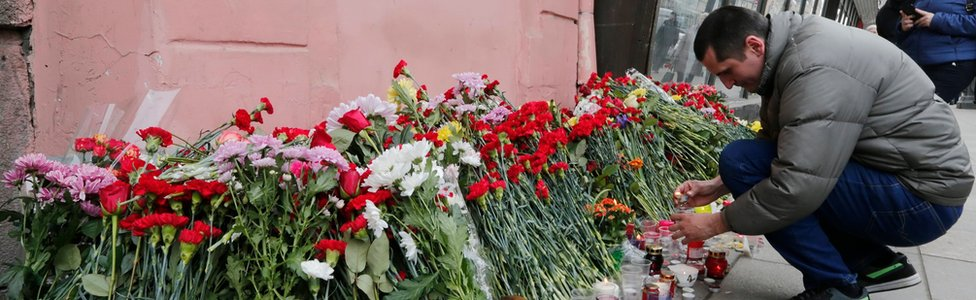 A man lays flowers outside Tekhnologicheskiy Institute metro station to pay tribute to the victims of an explosion in the metro station