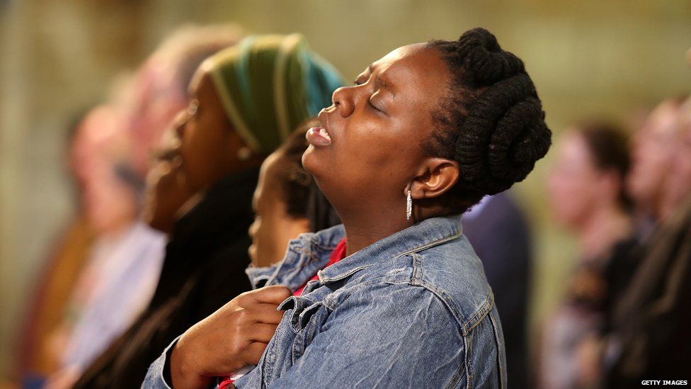 A mourner sings Nkosi Sikelel' iafrica following the death of Nelson Mandela in December 2013