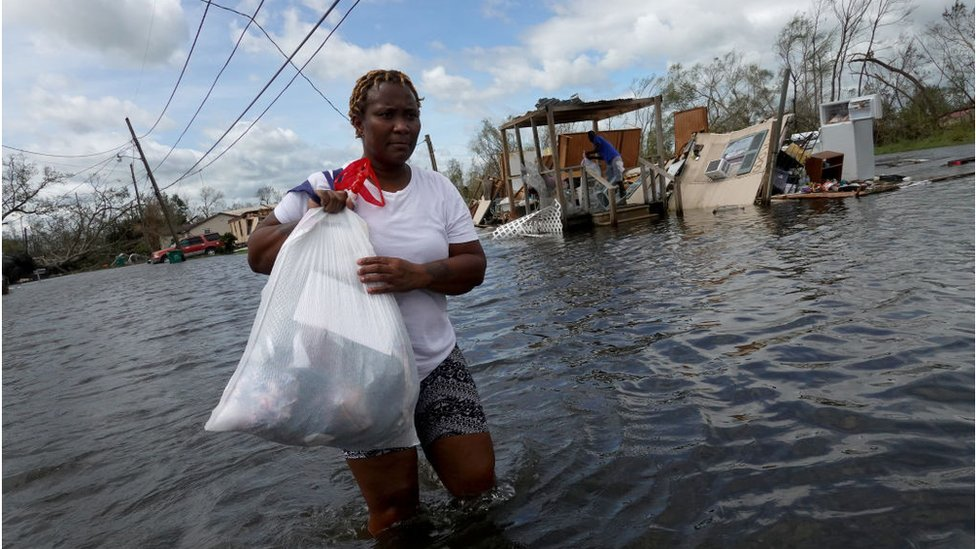 Una residente de Luisiana camina entre las aguas