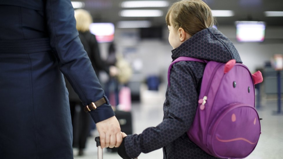 child with suitcase at airport