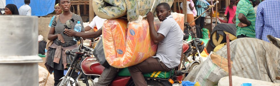 People on a motorbike with mattresses preparing to flee Juba, South Sudan - July 2016