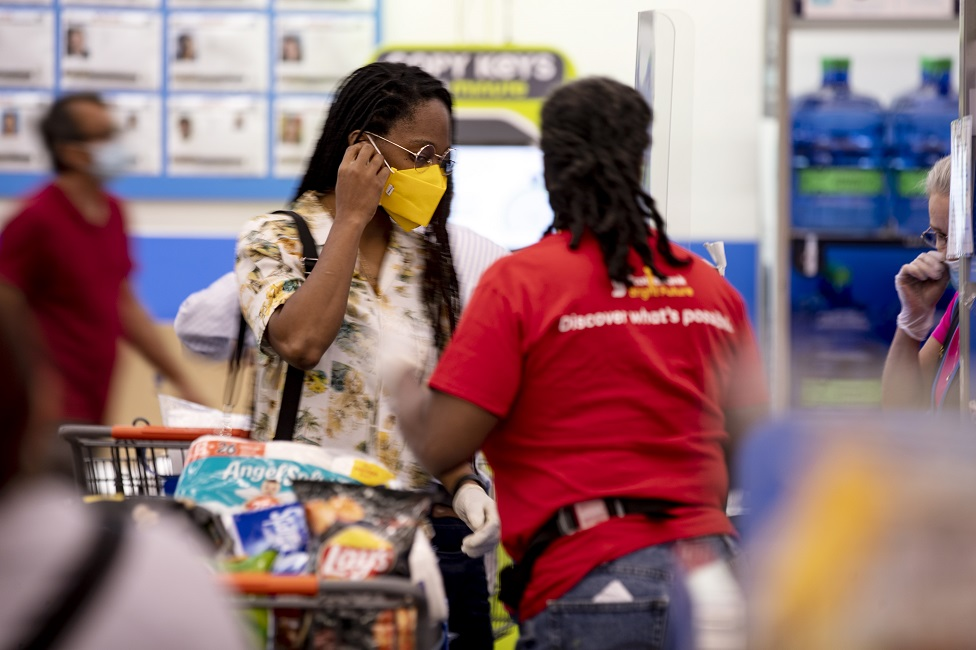 A Walmart shopper wears a face mask as protection against the coronavirus as she pays the cashier in a Walmart Supercenter in Burbank, California