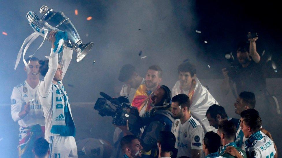 لاعبون من ريال مدريد يرفعون كأس البطولة