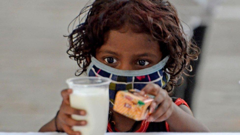 Un niño toma un vaso de leche y un paquete de galletas durante la distribución gratuita organizada por la policía de Kolkata en medio de una emergencia por el coronavirus en Kolkata, India, el 23 de mayo de 2021.
