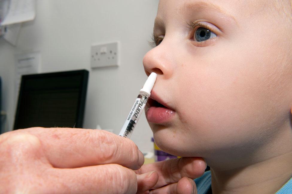 A young boy receiving the nasal-spray flu vaccine