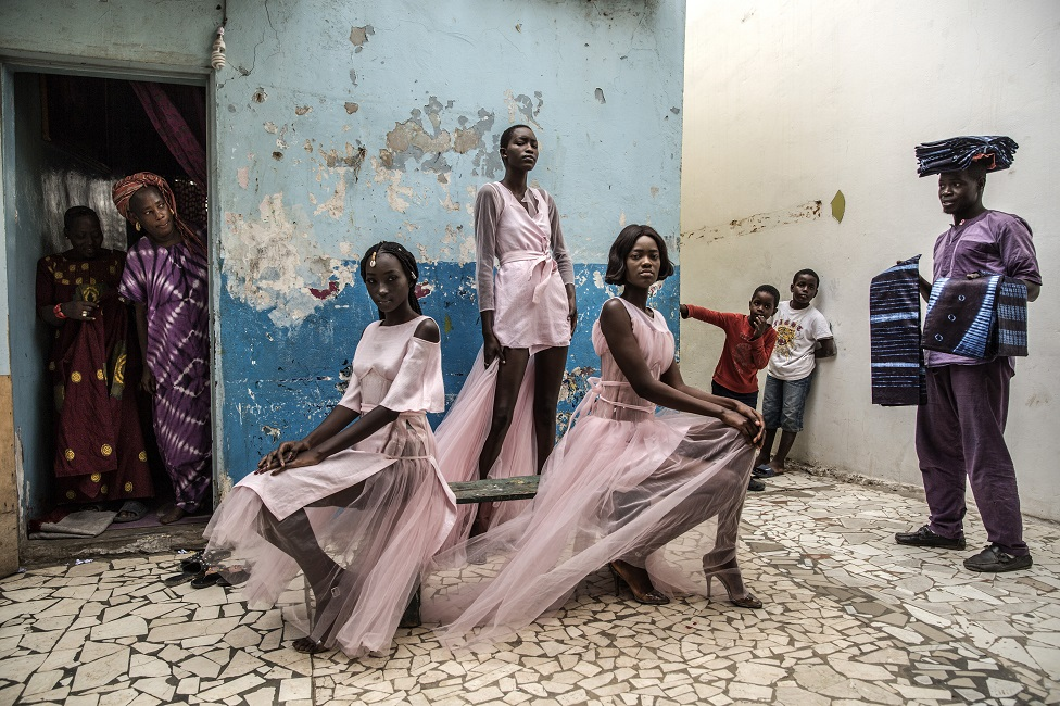 Models pose in the street wearing dresses