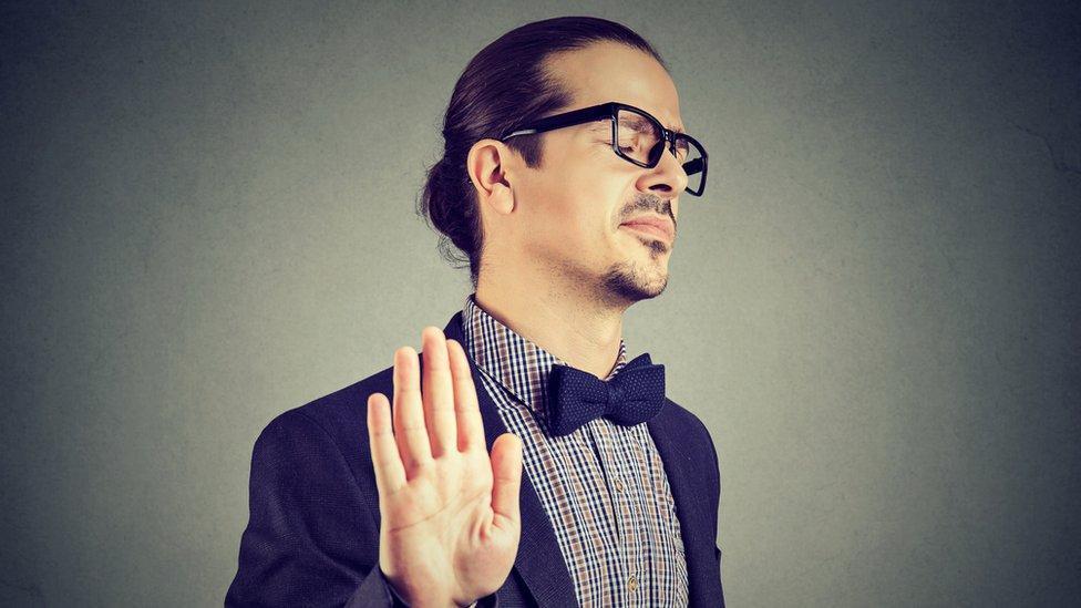 Hombre de traje con actitud arrogante.