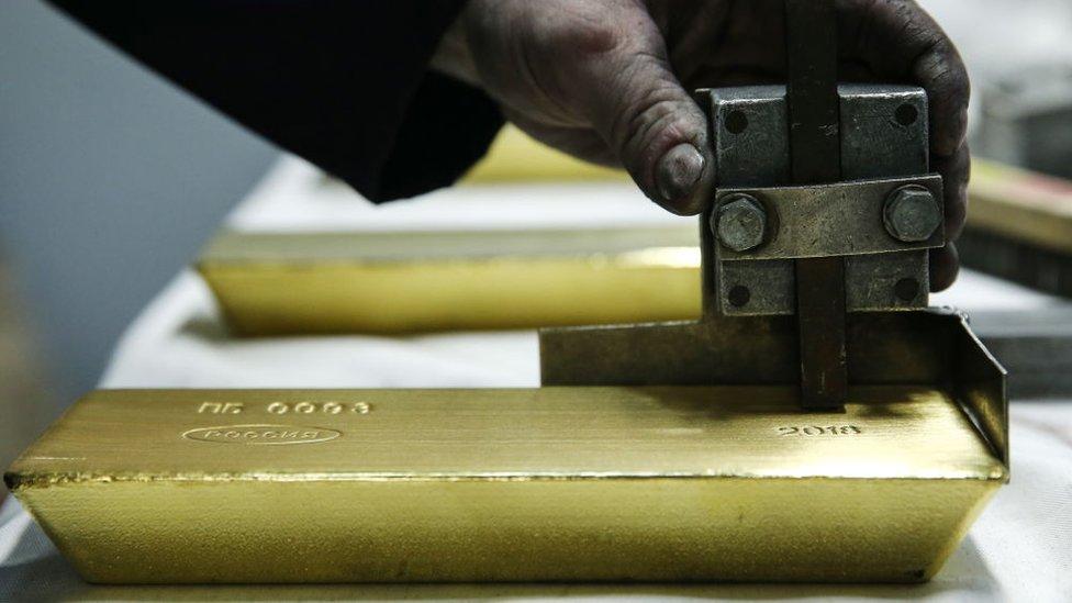Trabajador puliendo una barra de oro
