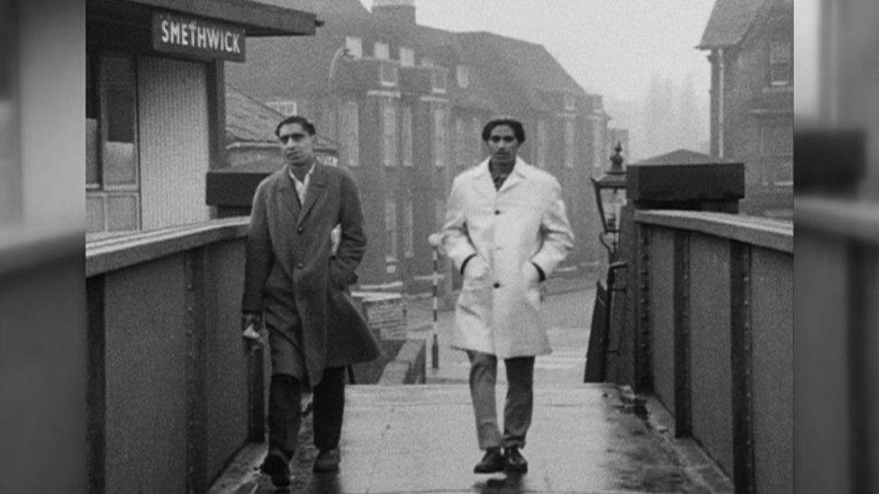 Two men walking along a bridge through Smethwick