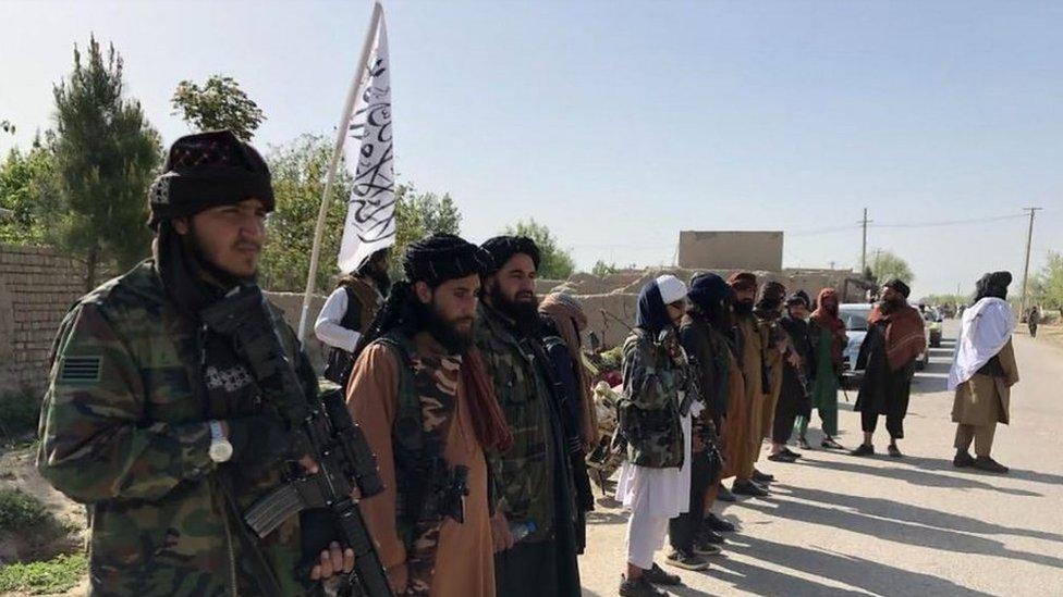 Milicianos del Talibán forman una fila al lado de una carretera