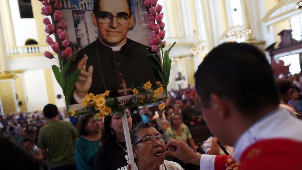 Una mujer recibe la comunión mientras carga una imagen de Monseñor Romero.