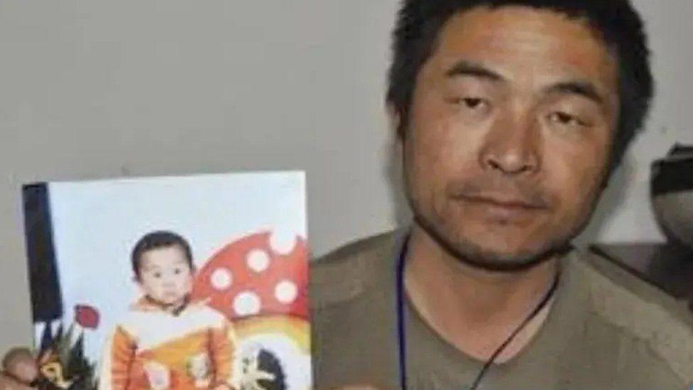Guo Gangtang junto a una foto de su hijo