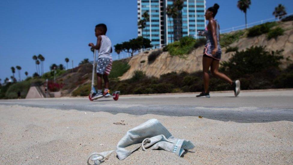 Una mujer y un niño paseando en Long Beach, California, mientras se ve una mascarilla en el piso.