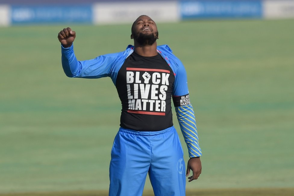 Cricketer Andile Phehlukwayo raises a fist and displays his Black Lives Matter T-shirt.