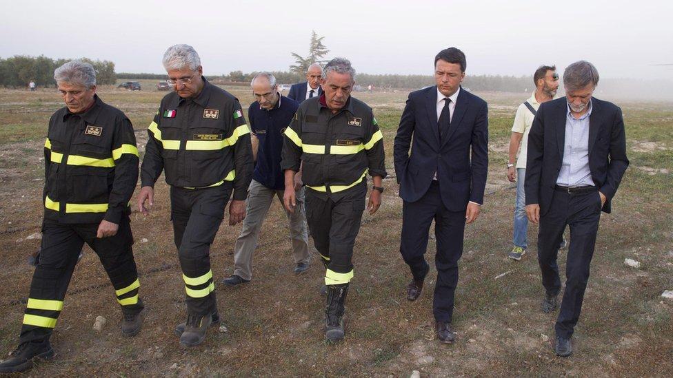 Mr Renzi walking alongside members of the emergency services, 12 July 2016