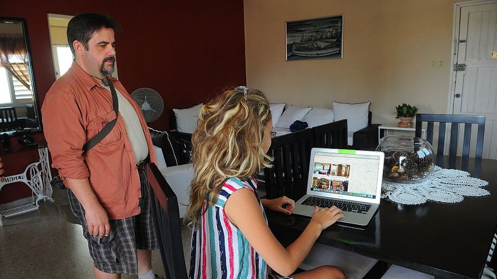 A Cuban woman provides a reservation service from a laptop in a rental house in Havana