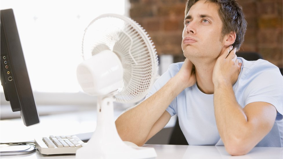 Man next to fan
