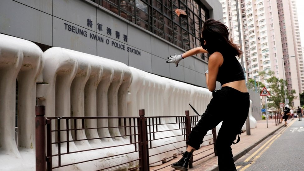 A woman throws a rock at a police station in Hong Kong