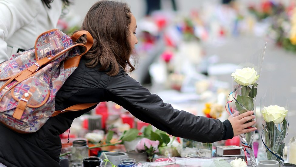 A women lights a candle on the monument of the 'Place de la Republique' where people continue to pay tribute to the Paris attack victims