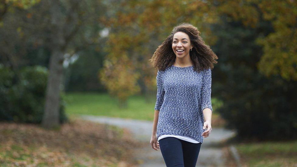 Una mujer camina por un parque