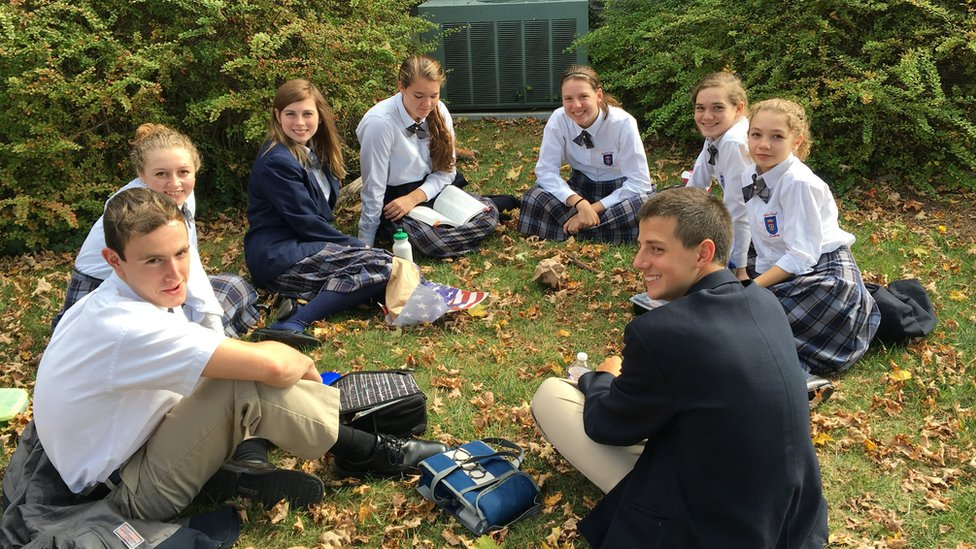 Schoolchildren sitting on the grass in a circle